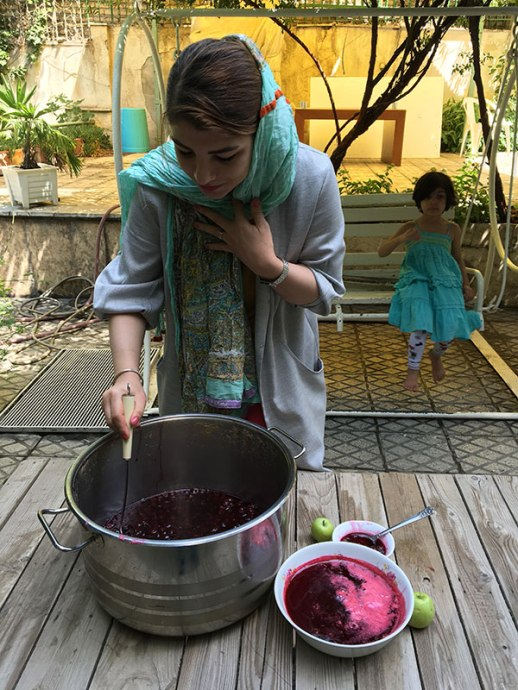 Persian girl & pot of sour cherry jam (moraba albaloo) in yard in Tehran Iran