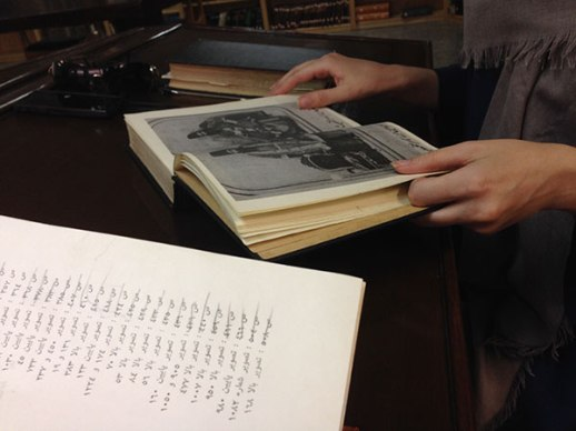 leafing through a historic Persian book at the library