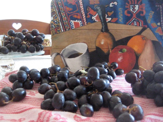 A photographic still life with real black grapes and a still life painting of a Persian rug, pomegranate, orange, pear, and a wooden bench with a heart shaped indentation. Painting by brother of Azita Houshiar