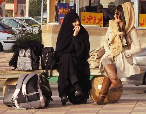 A woman wearing chador and another woman covering hair with a loose scarf | SOURCE