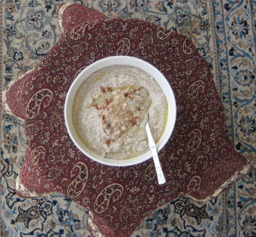 Bowl of halim (Persian wheat porridge) on termeh cloth & Persian carpet background