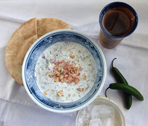 bowl of abdoogh khiar (Persian yogurt cucumber soup) with piece of bread   FigandQuince.com (Persian Cooking and Culture blog)