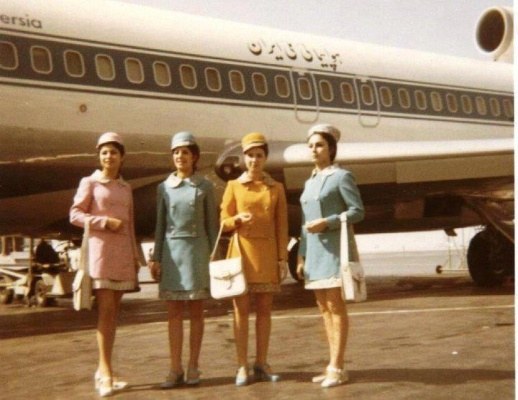 Iranian airline stewardesses wearing mini skirts in hues of pastel posing front of Persian airplane melli Iran