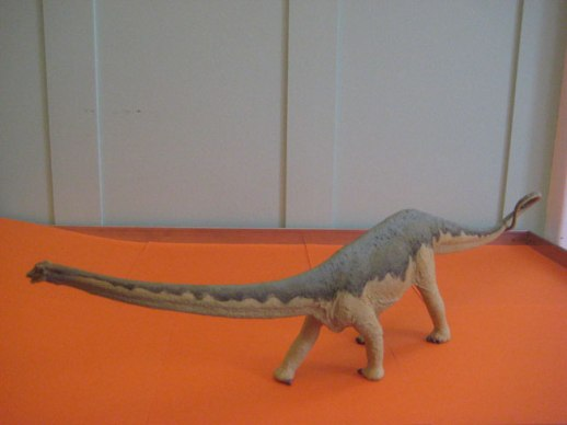 Dinosaur toy on orange background still life | @figandquince (Persian food culture blog)