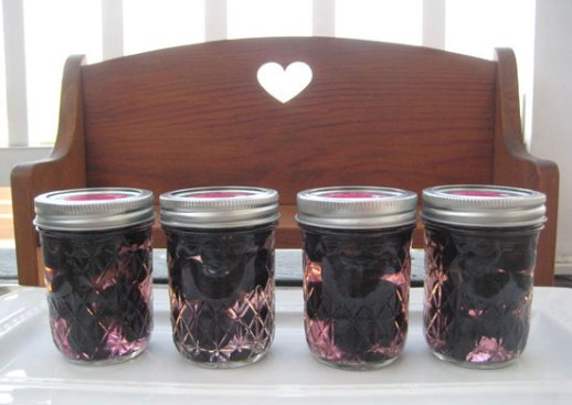 Grape pickle Persian torshi jars on wooden bench w/ heart shaped carving. Persian food blog recipe