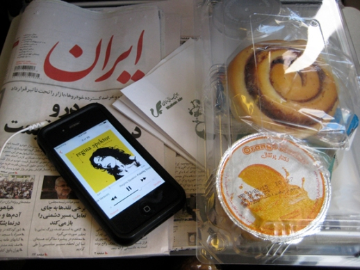 Still life with Iranian newspaper iPhone airplane snacks taken during flight in Iran