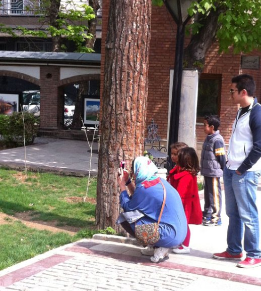 An Iranian family taking picture of a cat in the Bagh e Mouzeh ye honar (Iranian Art Museum Garden) in Tehran, Iran