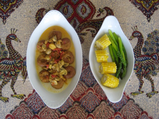 Persian koofteh (a type of flattened meatballs) served with corn and asparagus on a table cloth with a traditional 'galamkar' Persian design motif