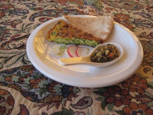 kookoo sabzi Herb kuku Persian food on paisley cloth Iranian fabric with tangerines