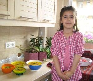 adorable little Persian girl in pink gingham outfit in kitchen with bowls of sholeh zard (yellow persian saffron rice pudding) rosewater Persian food blog (Fig & Quince) Iranian cooking and culture