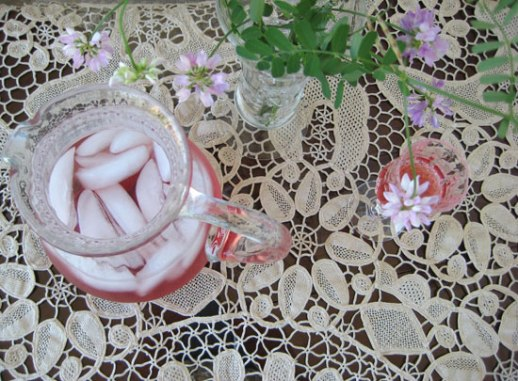 Pitcher and glass with ice and sour cherry syrup (sharbat 'e albaloo - Persian beverage drink) on lace doily tablecloth still life with food