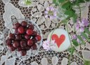 bowl of sour cherries and a red heart decoupage glass globe on doily lace table cloth with wild flowers still life with food Persian food blog