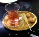 Persian tea cup on tray with rock candy and Persian almond cookie in cafe in Tehran, Iran