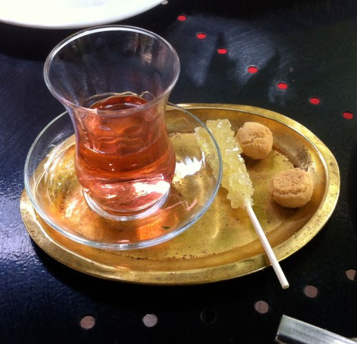 Chai chá cháy chayee Persian tea in estakn served with rock candy (nabat) and dainty almond cookied