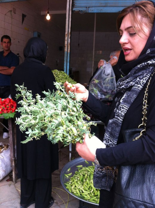 Persian woman in Kermanshah Iran bazar snacking on freshly harvested chickpeas