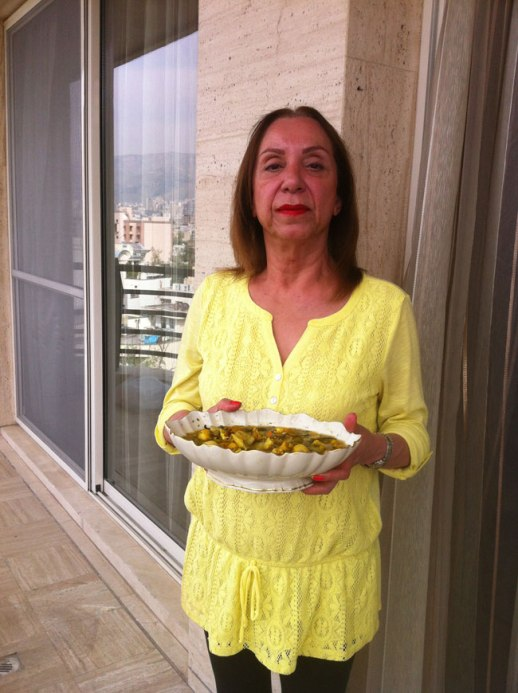 Iranian lady w bowl of homemade torshi (Persian pickles) on terrace of home in Tehran, Iran 2014