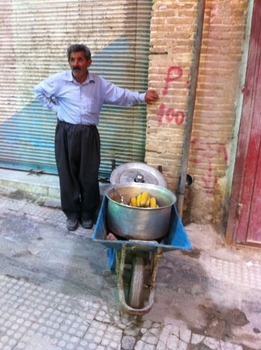 vendor with cart of persian grilled corn on the cob (balal) at Kermanshah Grand Bazaar, iran