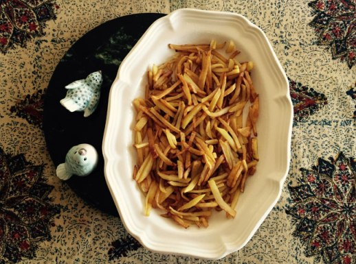 Homemade French Fries (ingredient for Persian khoresh gaimeh) in serving plate atop a Persian table cloth | @Figandquince (Persian food culture blog)