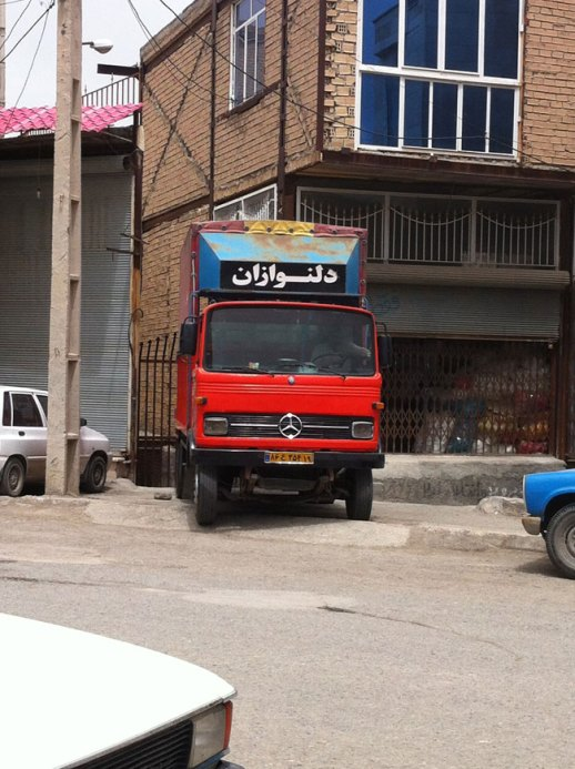 Red Mercedes Benz truk with Persian sign driving through Kermanshah, Iran 2014