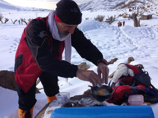 "Cracking eggs to make omelette camping style in snowy mountain top ""carrot field"" of Lavasan Tehran Iran"