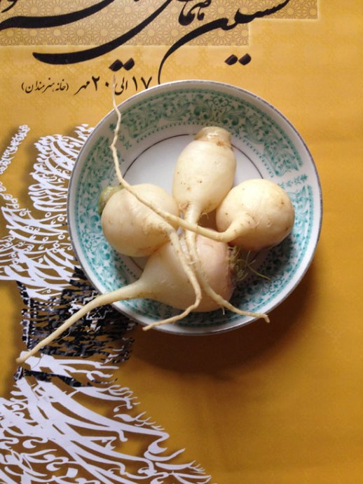A plate of cooked steam cooked turnips on Persian calligraphy background | @figandquince (Persian food culture blog)